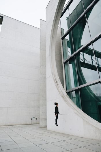 Side view of woman standing by modern buildings in city