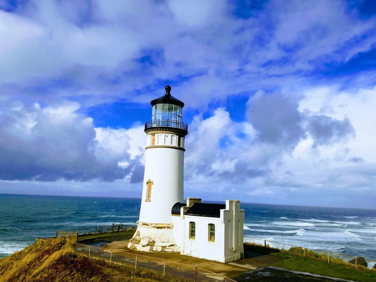 sea, sky, guidance, water, cloud - sky, lighthouse, architecture, built structure, building exterior, horizon over water, tower, horizon, beach, direction, land, security, building, nature, protection, no people, outdoors