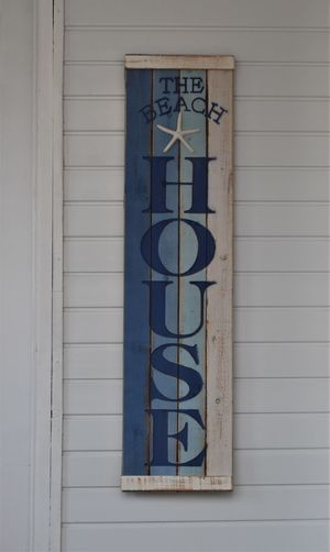 Blue and white striped colours on signage on a white clapboard building - The Beach House. Architecture Built Structure Building Exterior No People Wall - Building Feature Window Communication Day Building Text Outdoors Closed Glass - Material Western Script Blue Pattern Shutter Design Number Door Window Frame The Beach House Signage Signage On Building