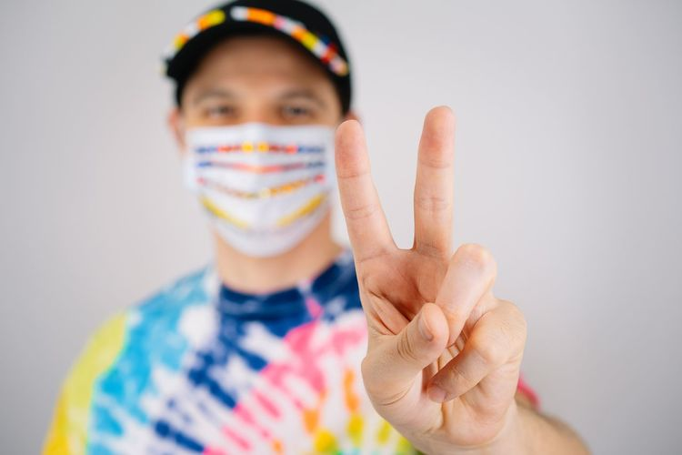 Portrait of man wearing mask and making peace sign against white background
