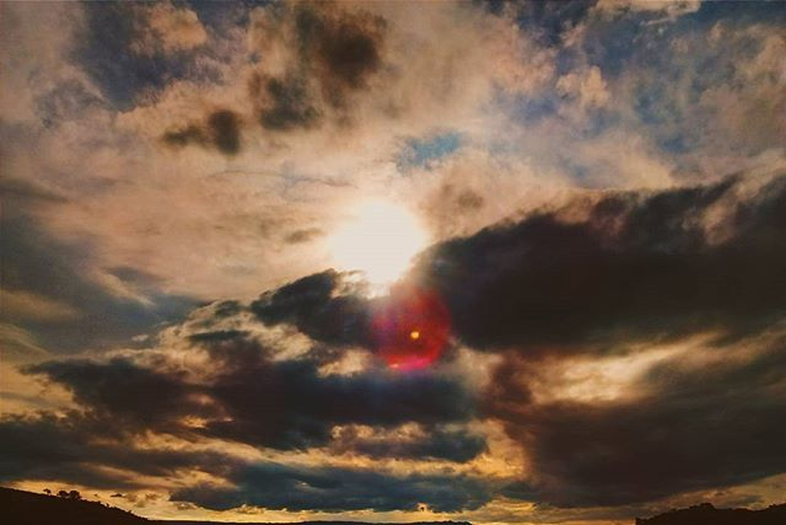 sky, cloud - sky, sunset, scenics, beauty in nature, tranquility, low angle view, tranquil scene, cloudy, nature, dramatic sky, sun, idyllic, silhouette, cloudscape, cloud, weather, orange color, overcast, majestic