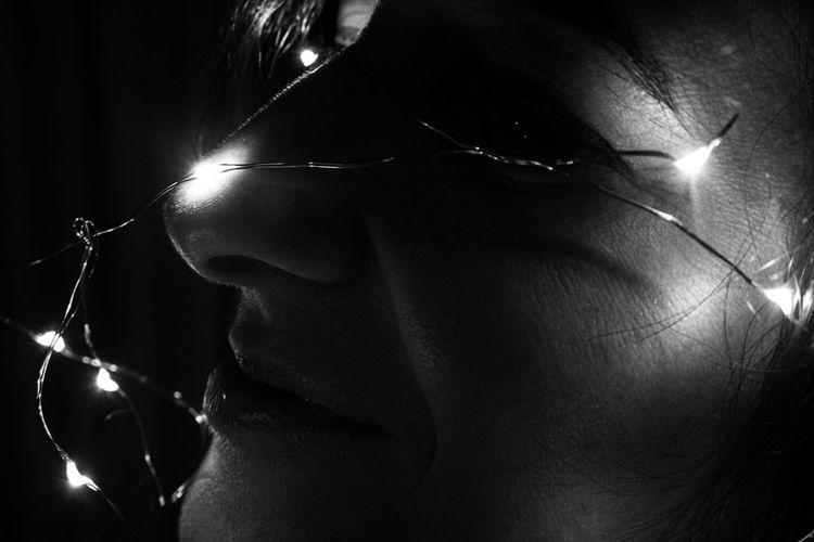 Close-up portrait of young man holding illuminated light