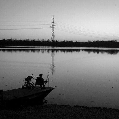 Silhouette Man Fishing In Front Of Lake And Electricity Pylon Against Clear Sky At Dusk