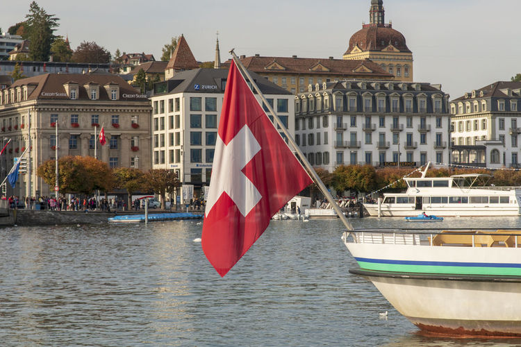Flag by river against buildings in city