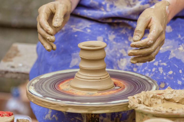 Midsection Of Woman Making Clay Pot
