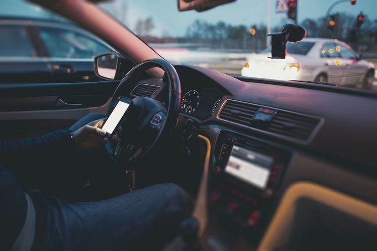Man using mobile phone in car while waiting in traffic