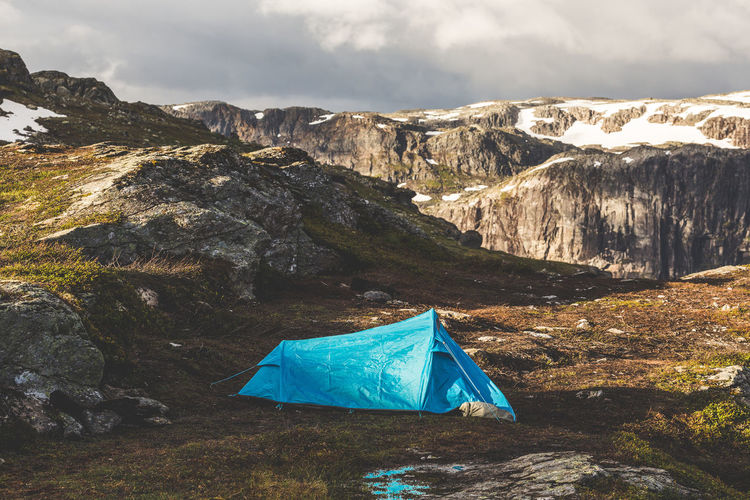 Tourist's tent stands in the mountains. summer sunrise above beautiful rocks in norway.