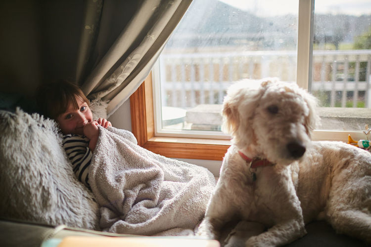 Woman with dog on window at home