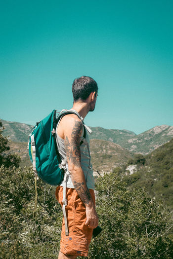 Young man looking at mountain range against clear sky