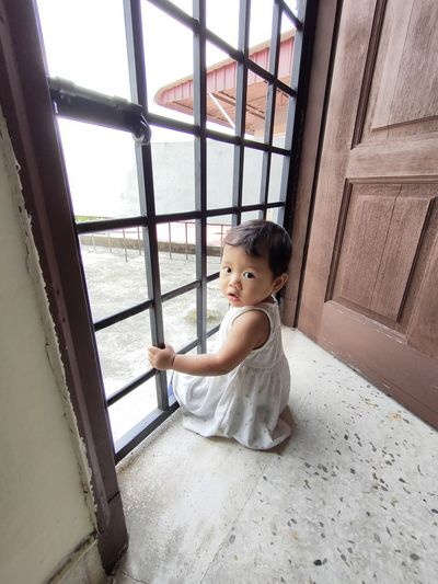 Portrait of cute girl sitting against window at home