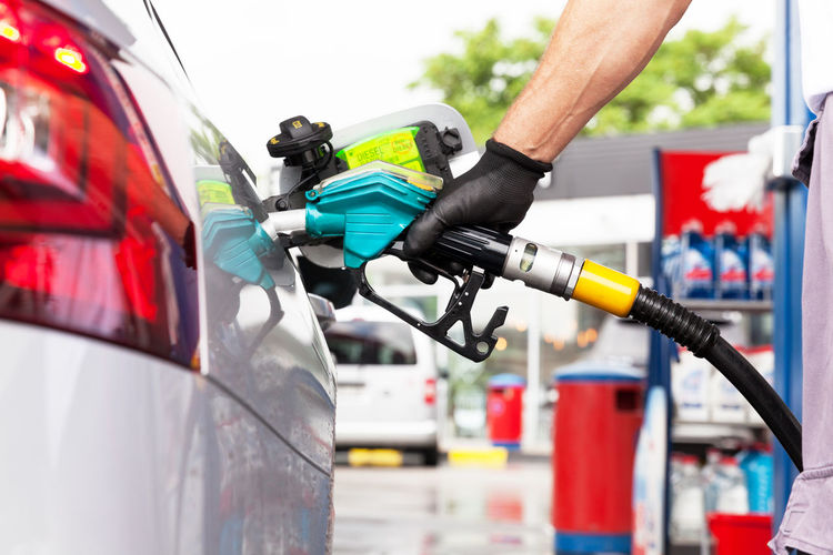 Cropped hand of worker refueling car at fuel pump