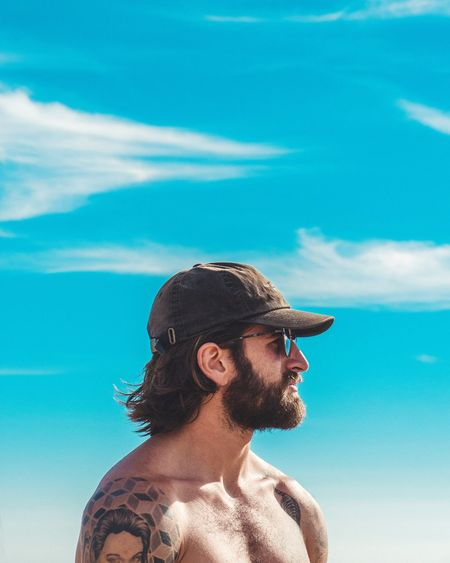 Shirtless Man Wearing Cap Against Blue Sky