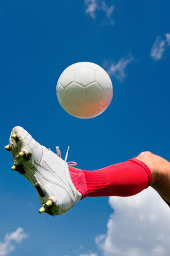 Soccer Player Kicking The Ball Soccer Football Football Player Soccer Player Soccer Ball Ball Soccer Shoe Sports Uniform White Playing Athlete Man Young Outdoors Team Sport Competition One Man Only Championship Strength Copy Space Red Blue Sky Kicking The Ball Leg Blue