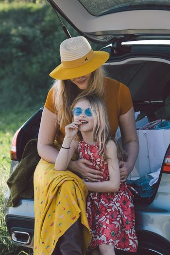 Cheerful mother embracing daughter while sitting in car