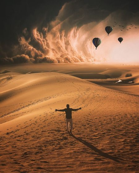 Rear View Of Man Standing On Sand Against Hot Air Balloons