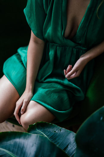 Midsection of woman sitting on sofa
