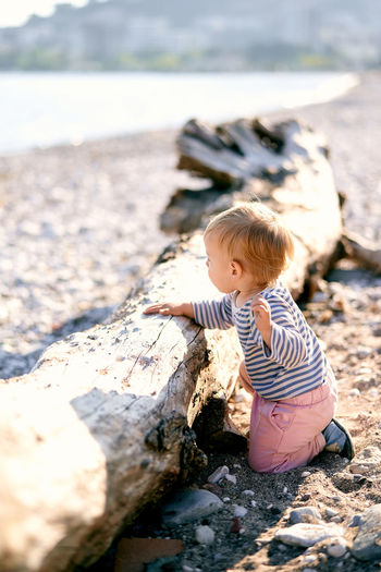Boy on rock in shallow water