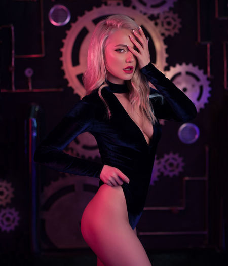 Fashion art photo of elegant blonde model in seductive wear with light neon colored club spotlights Adult Beautiful Woman Beauty Clothing Fashion Front View Hair Hairstyle Indoors  Leisure Activity Lifestyles Lingerie Nightlife One Person Real People Three Quarter Length Women Young Adult Young Women