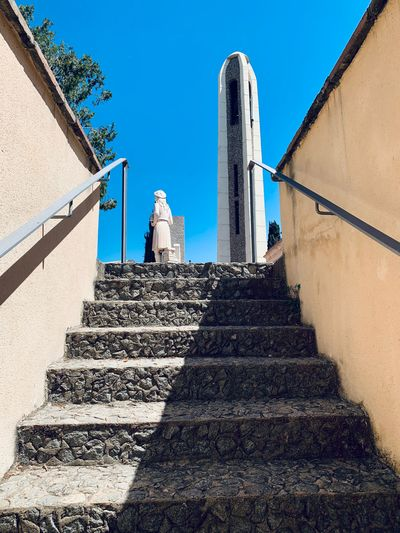 Low angle view of steps amidst buildings against sky