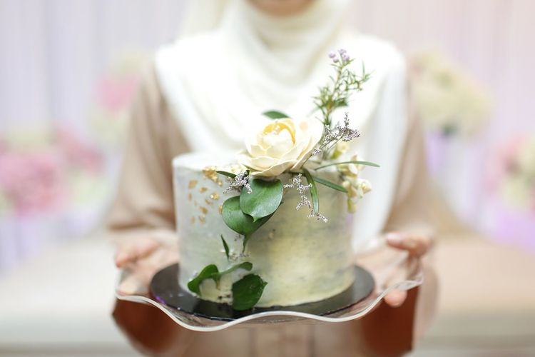 Midsection of bride holding wedding cake