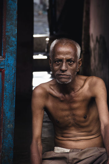 Portrait Of Shirtless Senior Man Sitting At Doorway