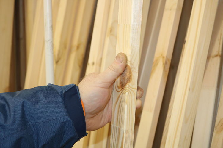Close-up of man holding wooden plank in workshop