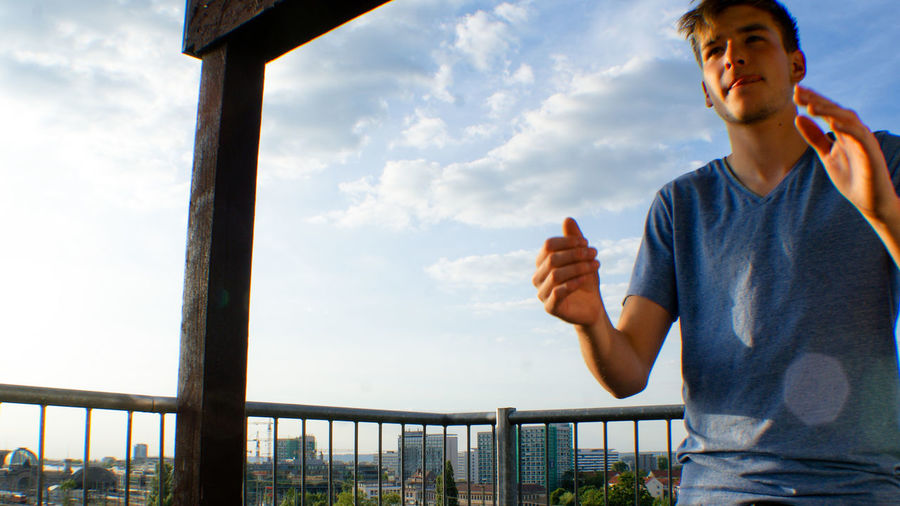 Low Angle View Of Young Man Standing In Balcony Against Sky