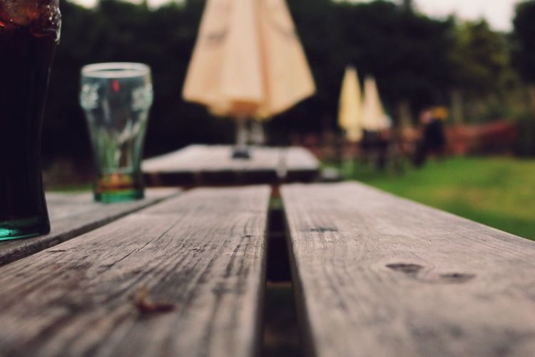 Drinking glasses on wooden table at field