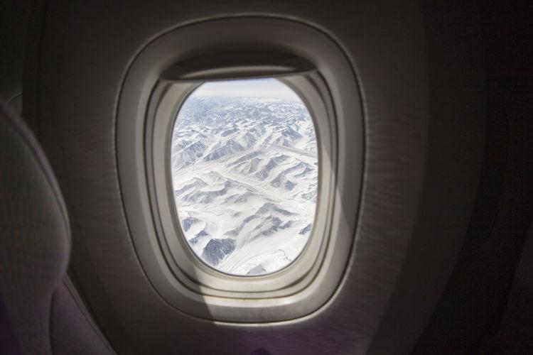 Snowcapped mountains seen through airplane window