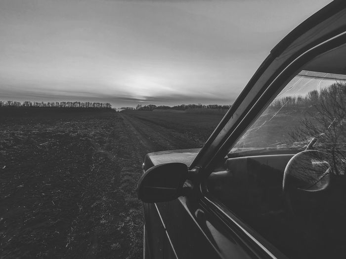 Car on road amidst field against sky