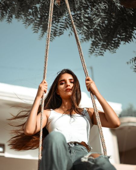 Portrait of young woman sitting on swing at playground