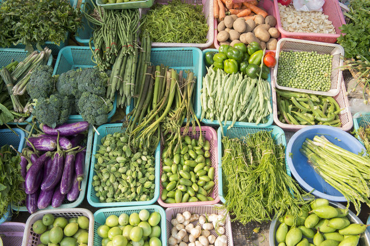 High angle view of vegetables in plastic containers at market for sale