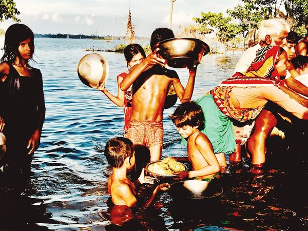 Siblings pass on food collected during floods in West Bengal, India Disaster Calamity Floods Water Group Of People Real People Lifestyles Togetherness Leisure Activity The Photojournalist - 2018 EyeEm Awards Enjoyment Nature Friendship Women People Emotion Celebration
