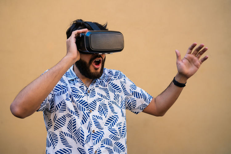 Young man wearing virtual reality simulator standing against wall outdoors