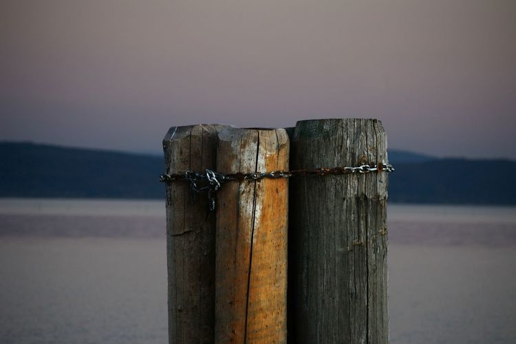 Close-up of wooden post in lake against sky