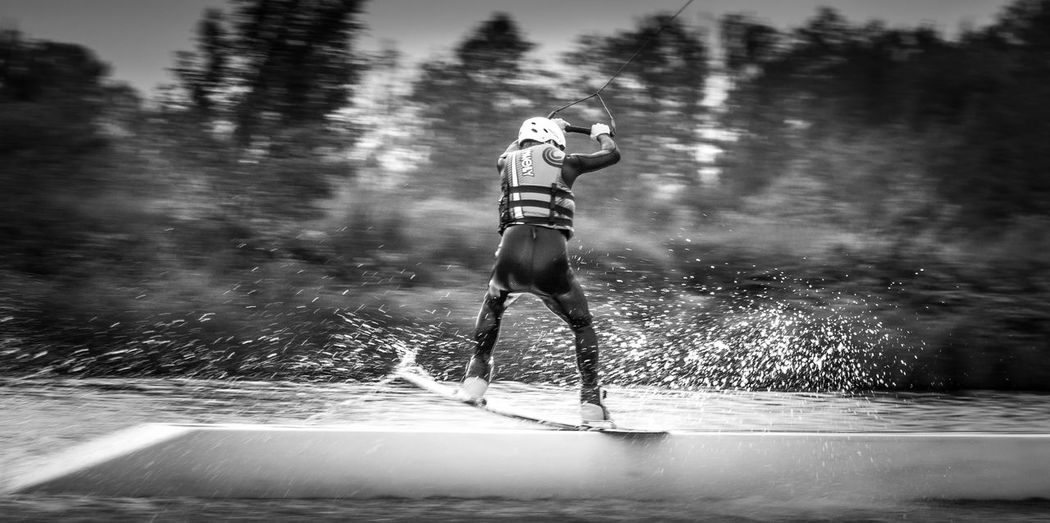 Full Length Rear View Of Person Wakeboarding In Sea