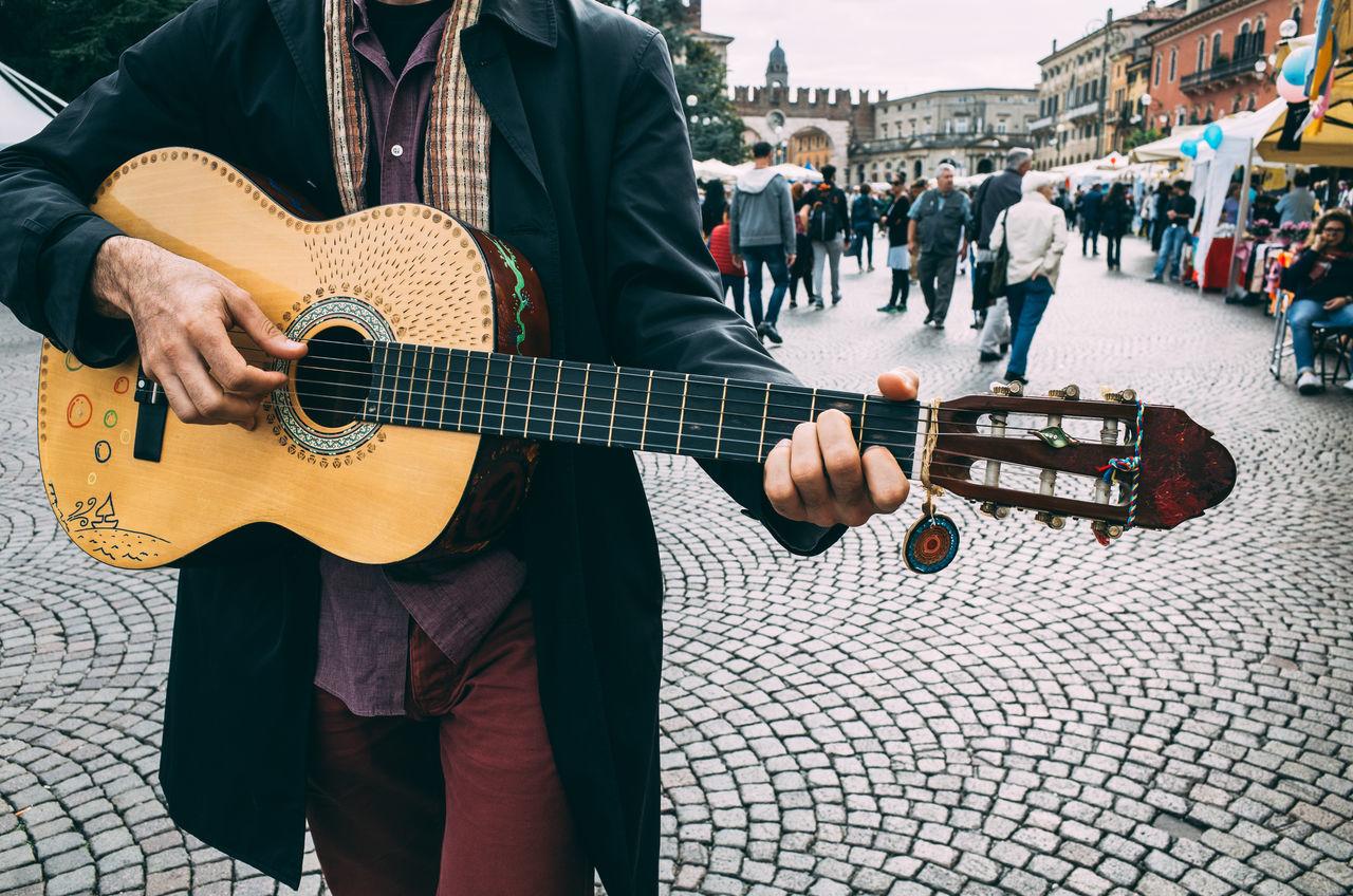 Man playing guitar on city street
