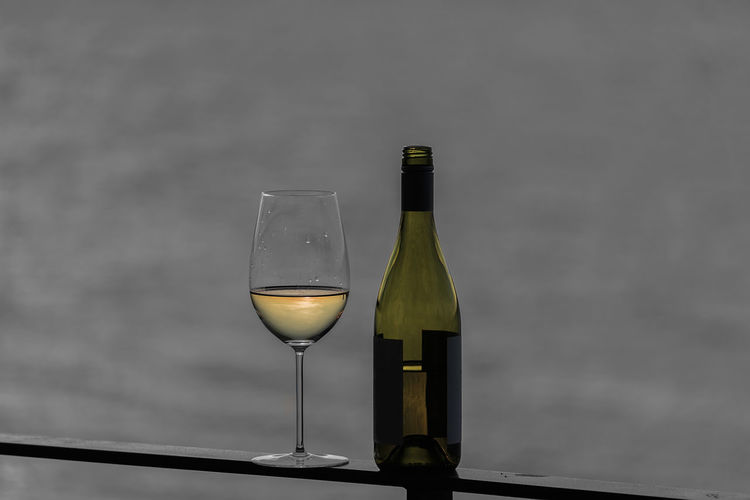 Close-up of bottle and wineglass on railing against sea