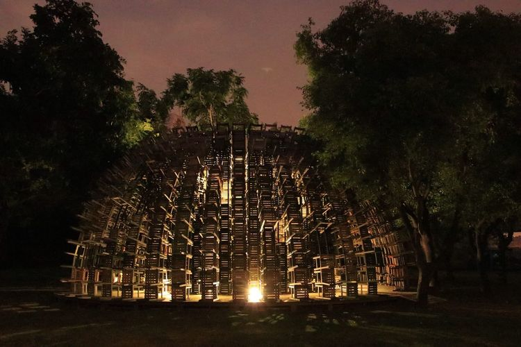 Built structure in forest against sky at night