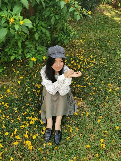 Full length of woman standing by yellow flowering plants