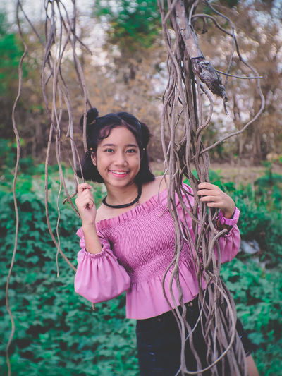 Portrait of smiling girl standing by vines of tree