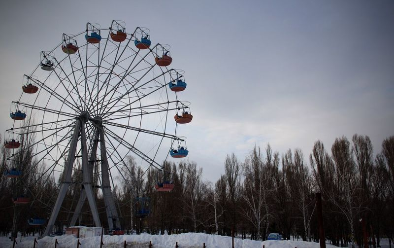 Low angle view of ferris wheel against sky during winter