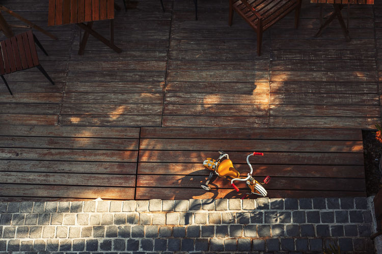 Directly above shot of tricycle on wooden floor