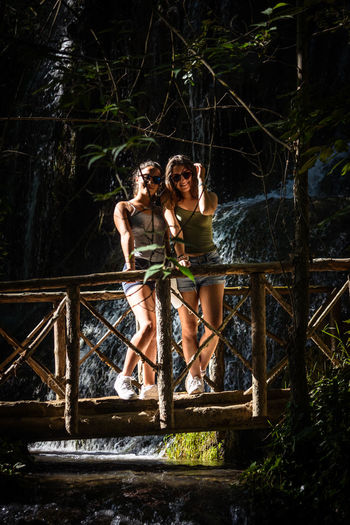 Portrait Of Smiling Friends Standing On Footbridge Over Stream In Forest