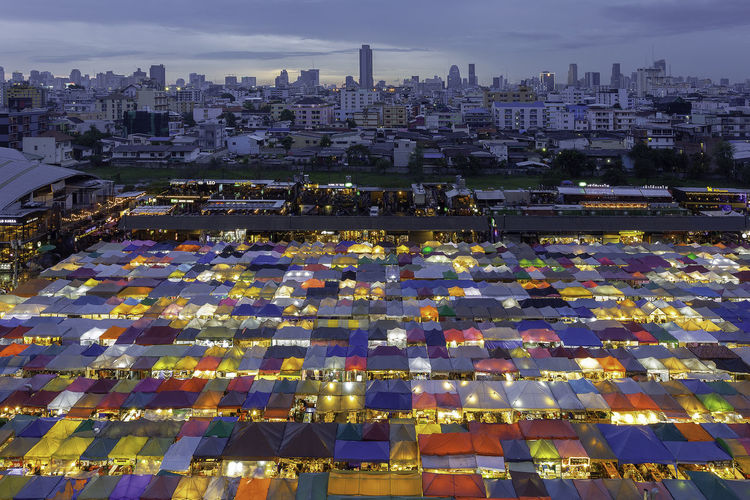 High Angle View Of Illuminated Colorful Tents Against Cloudy Sky At Night