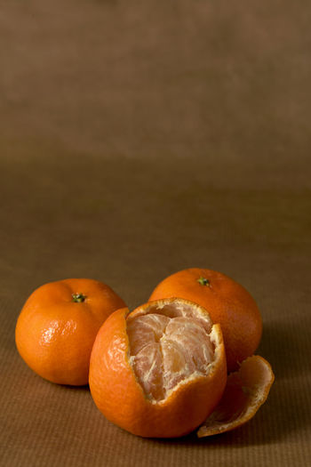 Close-up of three clementines on brown paper, with one half-peeled Citrus  Freshness Minimalist Brown Brown Paper Citrus Fruit Clementine Clementines Foodphotography Fruit Healthy Healthy Eating Healthy Food Ingredient Mandarins Minimal Minimalism Monochromatic Monochrome Mood Obst Orange Color Peel Peeling Pile Still Life