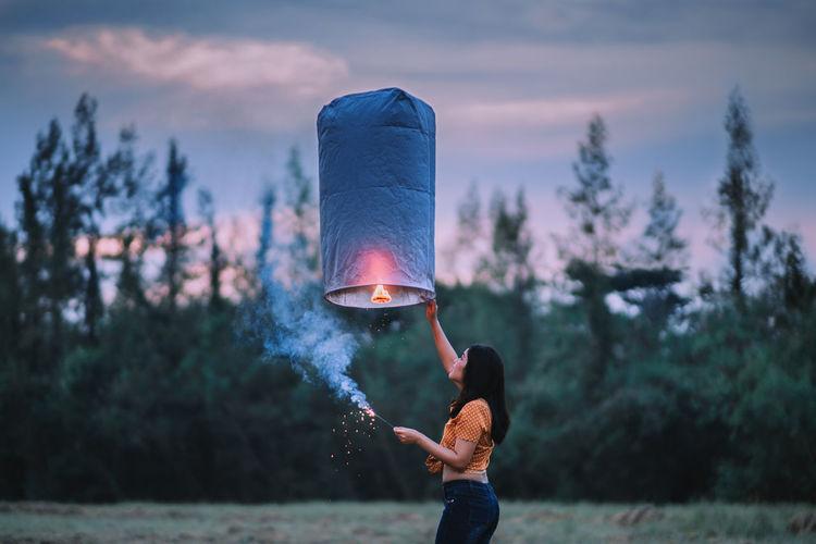 Side view of woman holding illuminated paper lantern