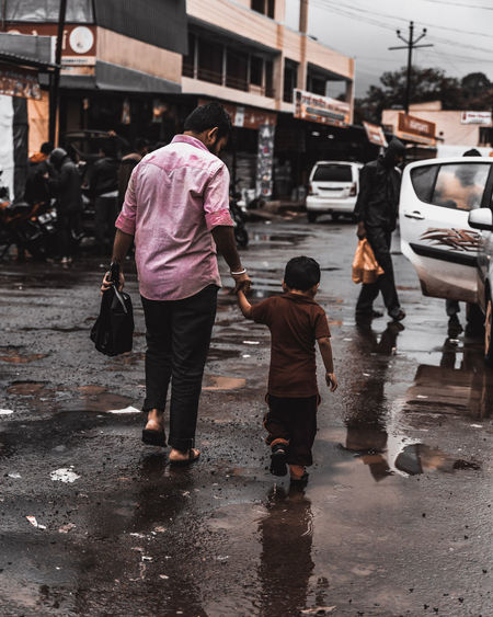 hold hands Streetphotography Street Photography Childhood Children Only Rural City Full Length Wet Street Rear View City Life Rain Weather Architecture Monsoon Umbrella Raincoat Rainfall Puddle Rainy Season Single Parent