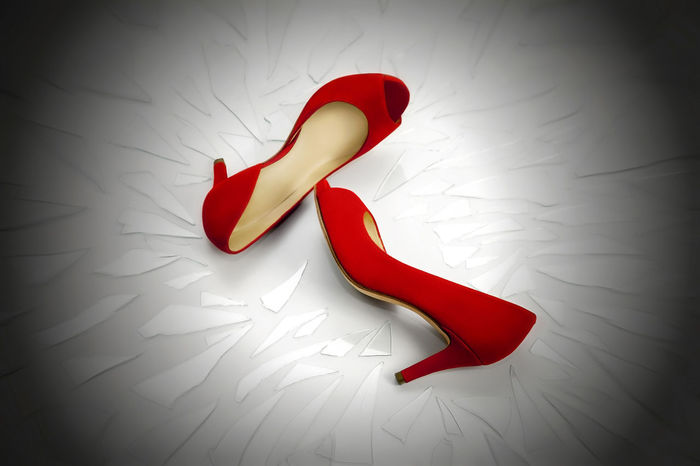 Two women's shoes red, rest on a plan full of broken glass fragments. The image symbolizes the continuing violence suffered by women who often end up victims of family killings. Close-up Glass Fragments Red Red Shoes Simbol Still Life Victims Vignette Violence Womans