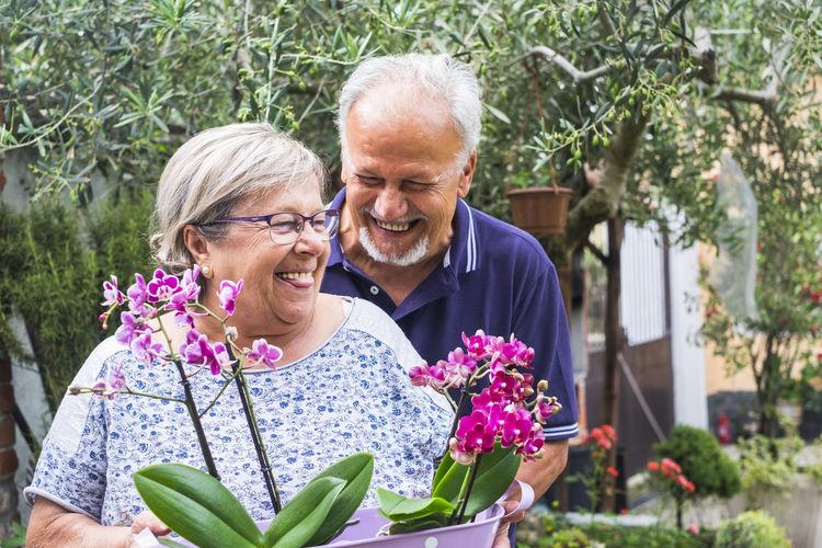Smiling Senior Couple Holding Plants At Back Yard